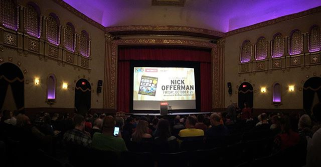 Shook Nick Offerman's Man-Hand.  Image description: view from our seats at the Michigan Theater in Ann Arbor, MI. The backdrop screen shows a cover of Nick's book 'Good Clean Fun'. There are rows of people on front of us and wall sconces and a chandelier lighting the beautiful, ornate theater.