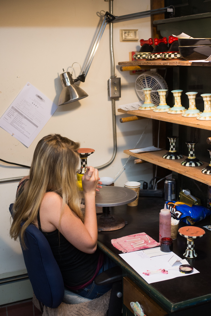 An artisan carefully places 18K gold on her candlestick.