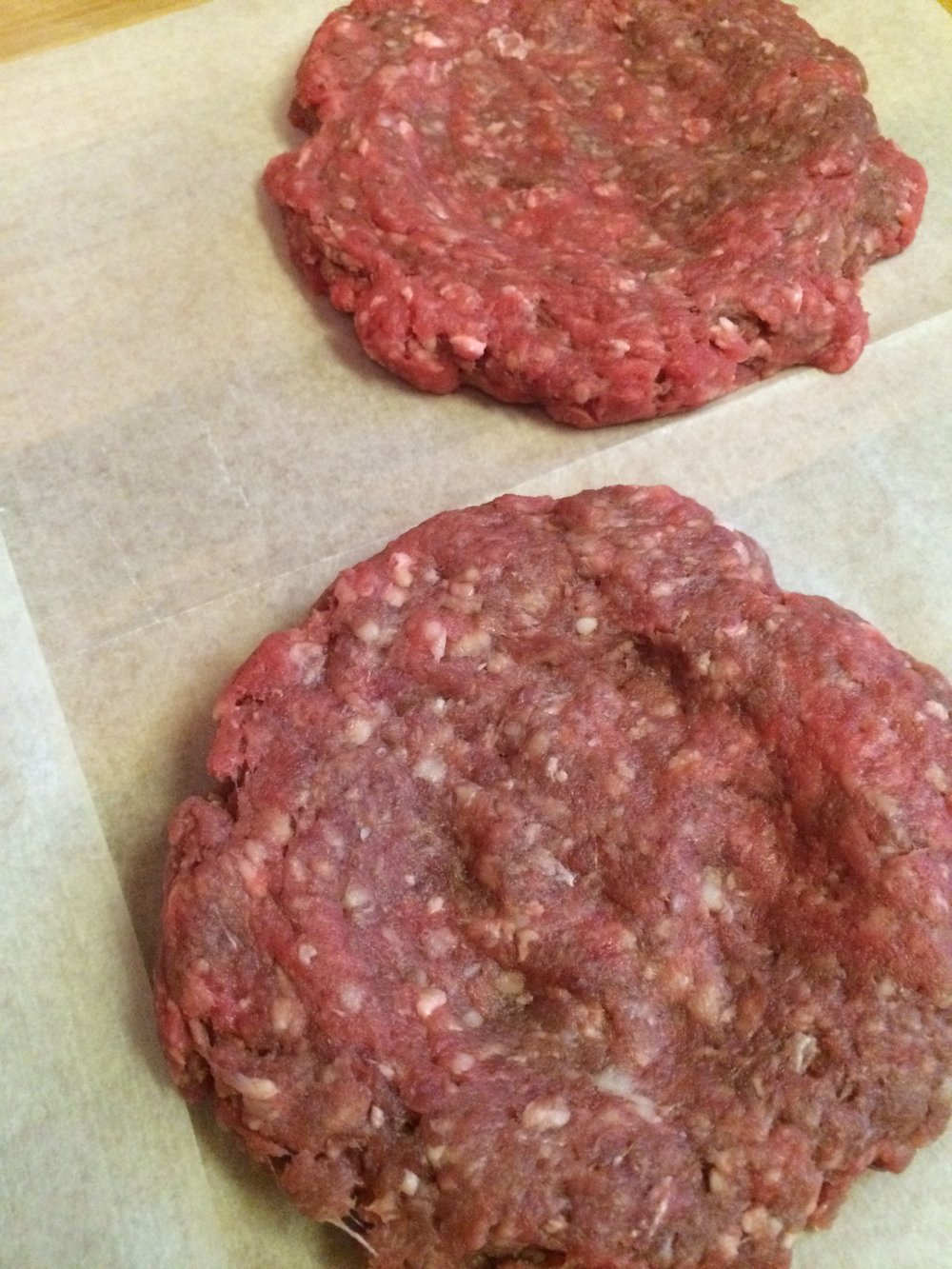 Make an indentation by flattening the center of the burger a bit thinner than the rest to house the filling