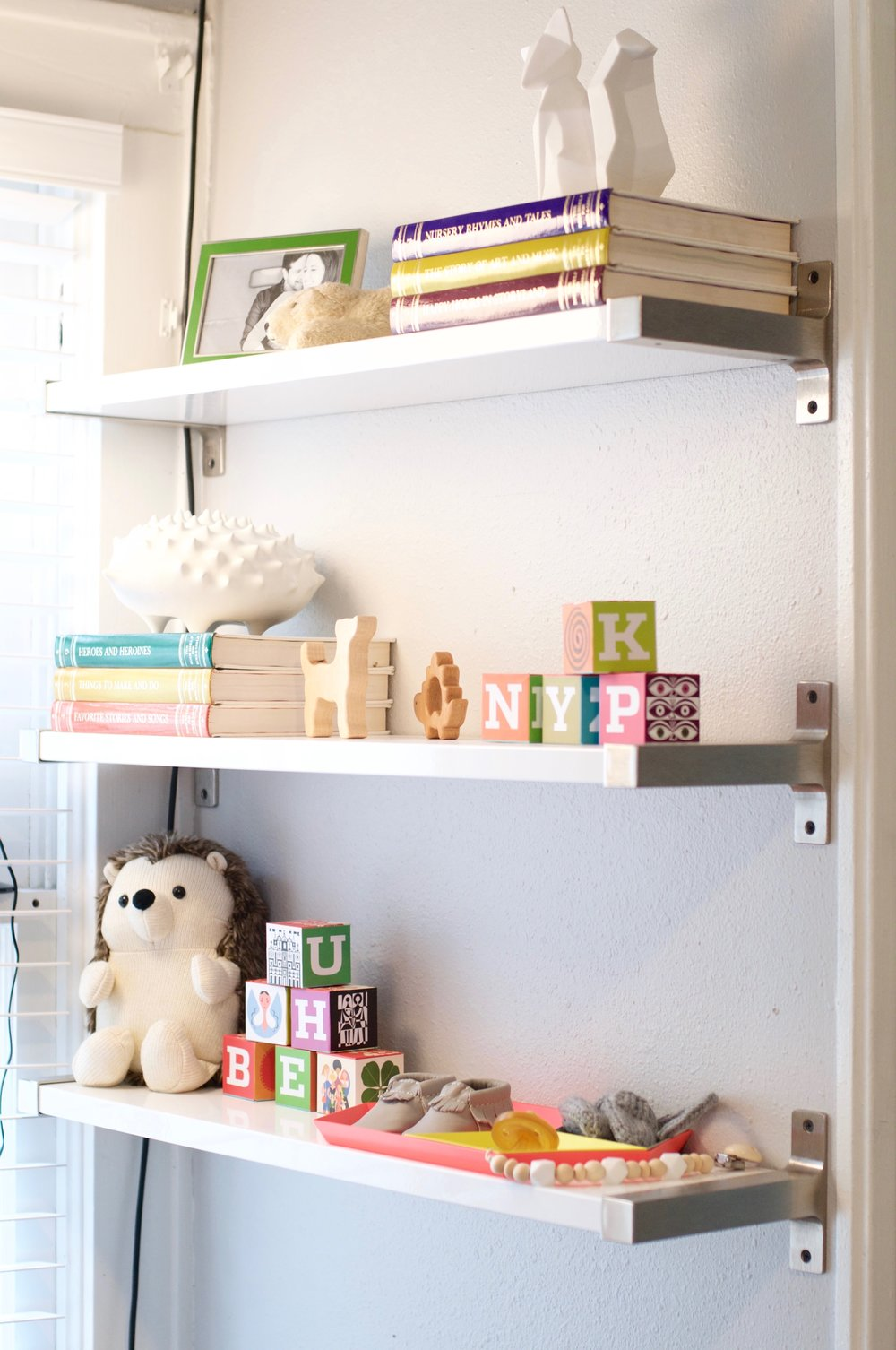 blocks  |  shelves  |  hedgehog stuffie  |  dog rattle  |  dino teether  |  trays  | fox (old Target find) |  moccasins  |  pacifier  |  pacifier clip  |  mittens  | porcelain hedgehog (old Jonathan Adler find) | green frame (old HomeGoods find)