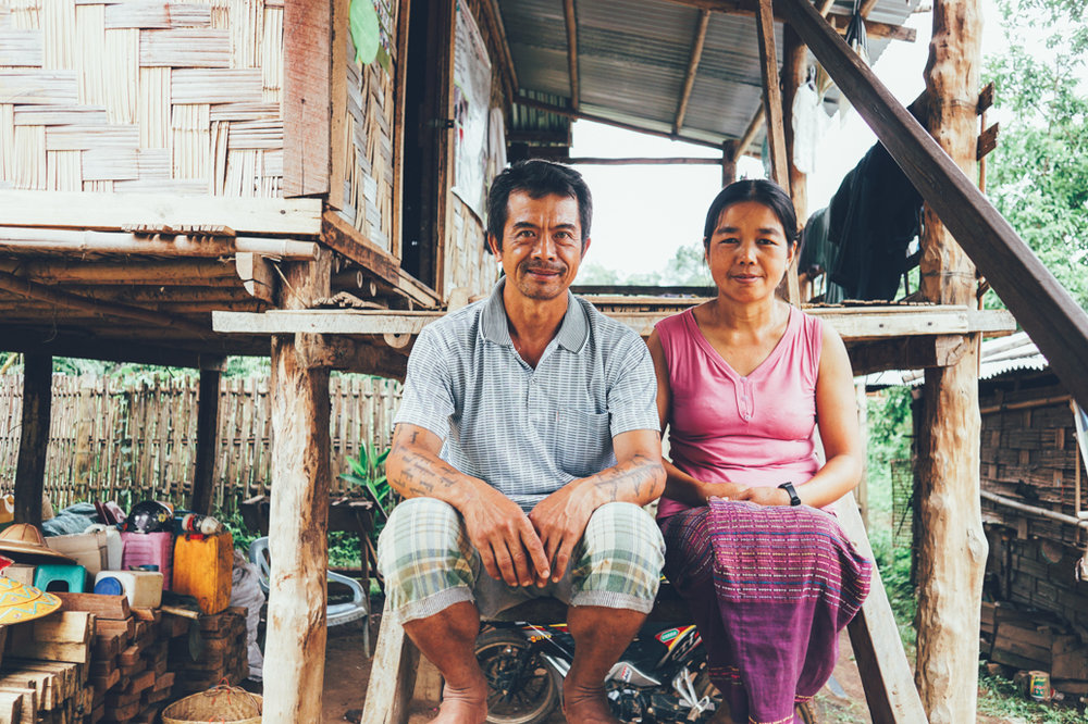 Shan village leader and his wife at the front steps to their home.