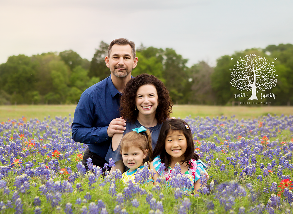 Schmedthorst Family in a patch of bluebonnets at eye level.