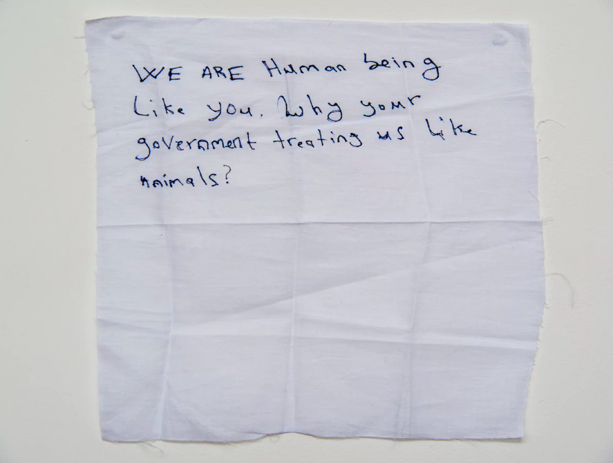 'We are human being': a hand written note from  a detainee on Manus Island .  Photograph: David T Young/ Penny Ryan