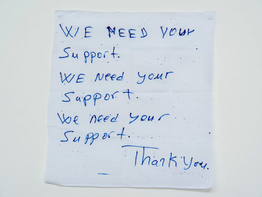 'We need your support': a hand written note from  a detainee on Manus Island .  Photograph: David T Young/ Penny Ryan