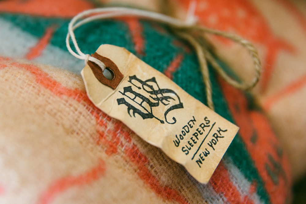 Inspired by old tags found around the handles of vintage military bags and other luggage, each hang tag is hand stamped and distressed using a five step treatment (seriously). A special brass pin is tied on (Davis has the blisters to prove it) and attached to every item in the shop.