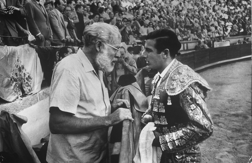 "Spanish matador Antonio Ordóñez getting a pep talk from long time friend Ernest Hemingway before a bullfight in 1959.  If Hemingway gave Ordóñez the same advice he gave friend A.E. Hotchner  the day Hotchner became a matador , it went something like this:  ""You only have to do three things. Number one: Look tragic... Number two: when you get to the ring, people are watching you. Don't lean on anything; it's ugly for the suit. And number three: if the photographers come toward you, put your right foot forward; it's sexier."""