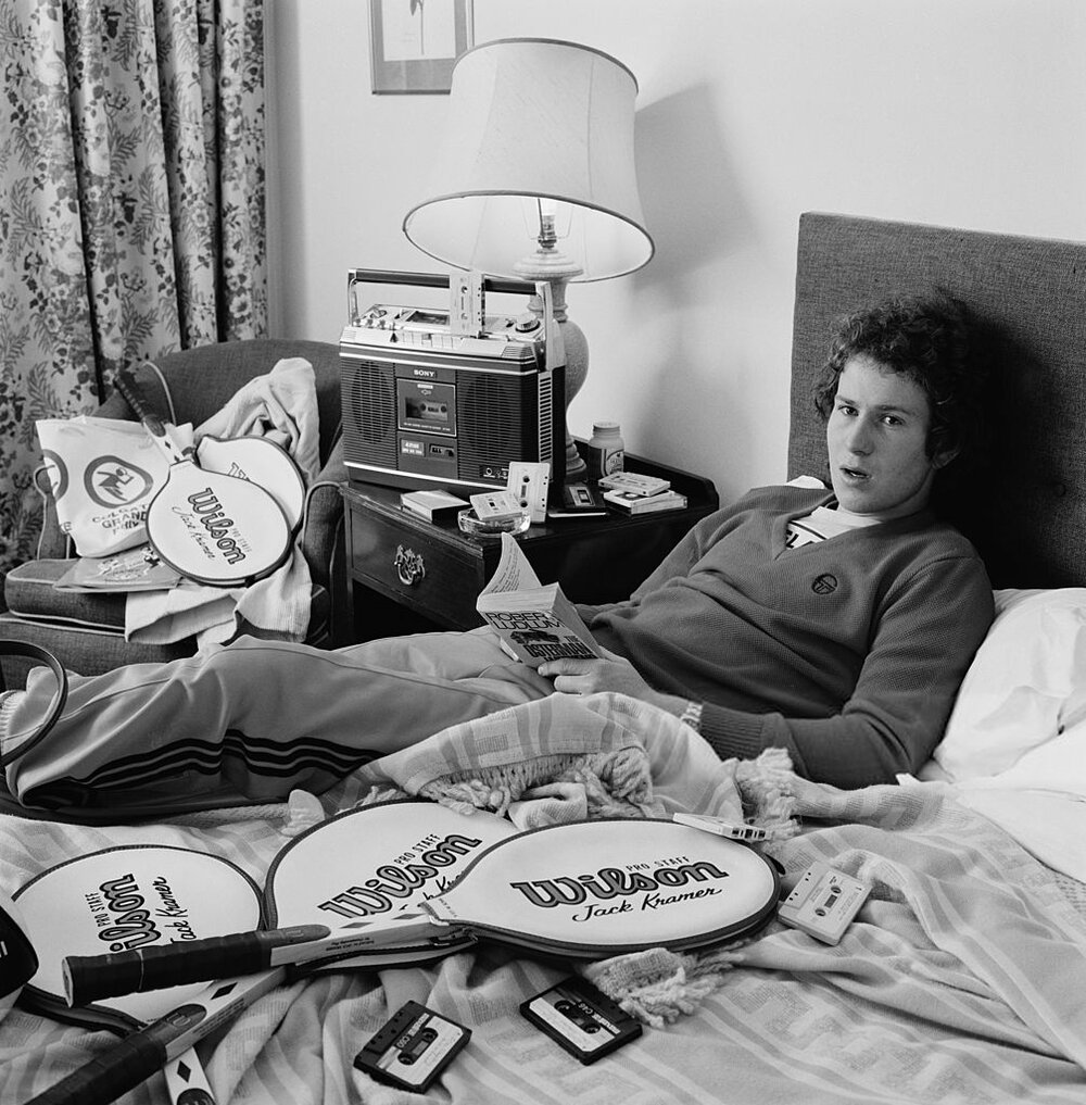 A 20 year-old John McEnroe relaxes at home* in 1979. He would go on to win the U.S. Open that same year.     *That lamp probably  called his ball out .