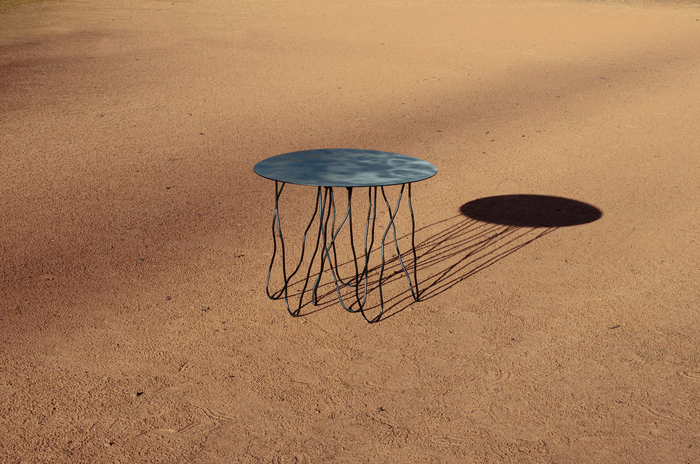 """QUALLE // The round side table has an iron tabletop resting on seven individually formed round bars. The """"playfully"""" decorative table legs were welded onto the table top using a sophisticated method which allows the weldseams to remain invisible to the viewer. Colors: Orange, Black, Ivory. Height ca. 43cm, ø ca. 54cm."""