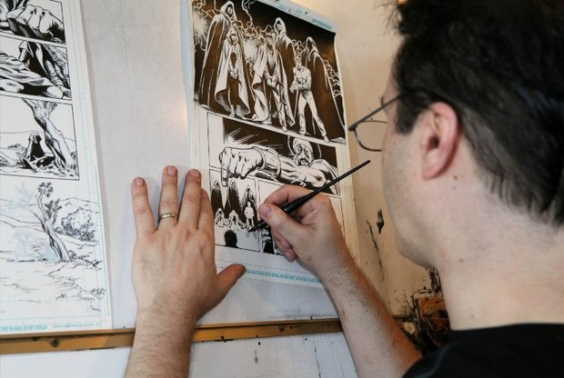 Scott Hanna inks a comic book panel at his home studio in Riegelsville. (LehighValleyLive.com Photo)