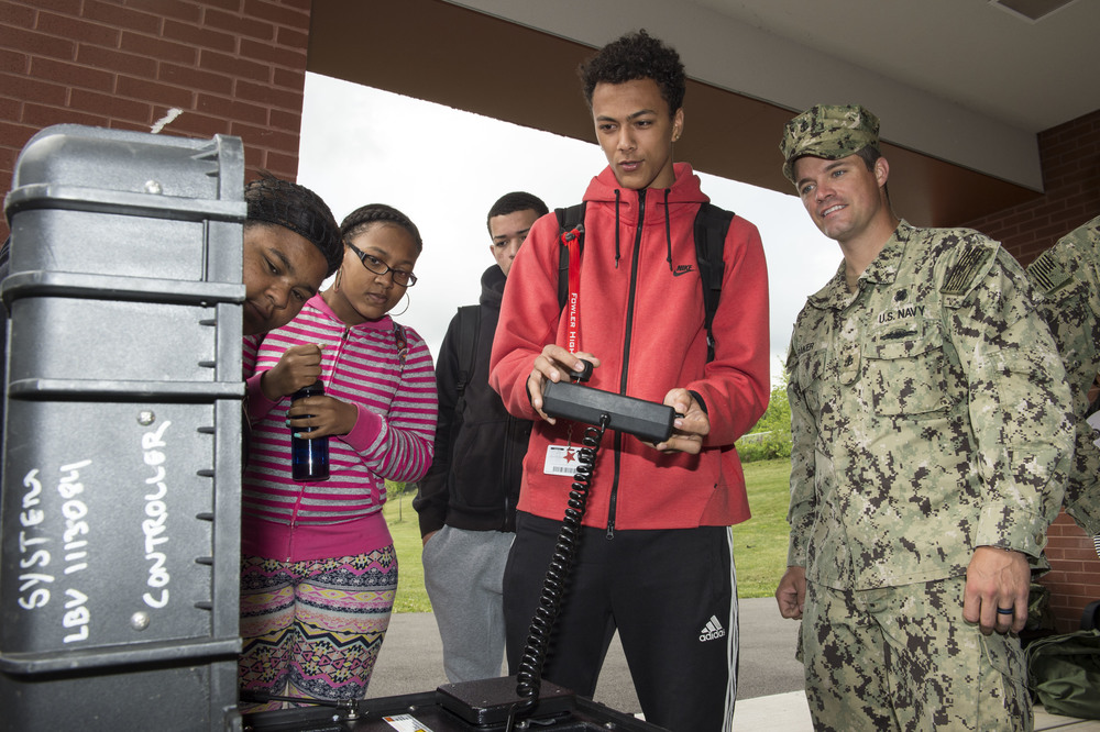 SYRACUSE, N.Y. (June 8, 2016) Chief Navy Diver Josh Baker assigned to Explosive Ordnance Disposal (EOD) Group 2 looks on as a student at Fowler High School works the controls of a Seabotix underwater robot during an EOD demonstration at the school as part of Navy Week. (U.S. Navy photo by Mass Communication Specialist 1st Class Nardel Gervacio/Released)