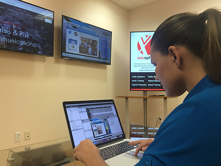 Vox Optima digital signage expert working on new client campaign content.