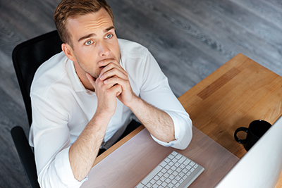 graphicstock-top-view-of-pensive-young-businessman-working-with-computer-and-thinking-at-workplace_BuxepozSnx.jpg