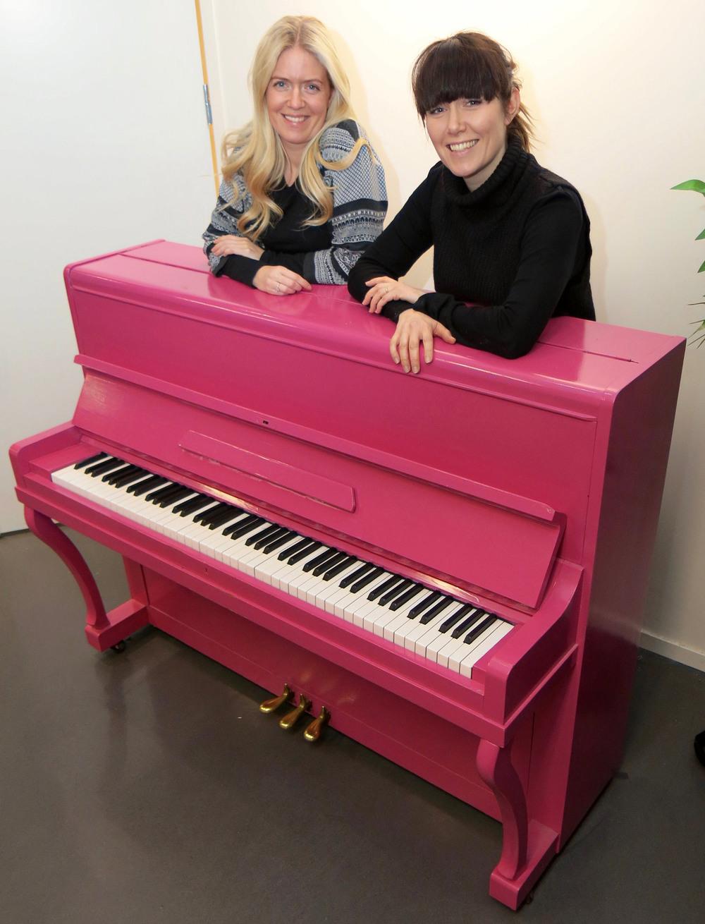 FØDT PÅ NY:  Pianoet fant de gratis på Finn.no. Da var det brunt og trist. Nå er det rosa. − Ungene er helt ville etter å spille på det, sier eierne av Showskolen, Guro (t.v) og Marte Helleseter.