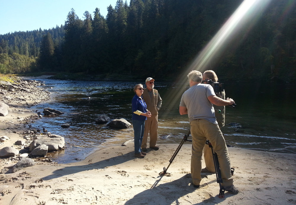 """Linwood Laughy (white beard) and his wife, Karen """"Borg"""" Hendrickson, talk with reporters along the Lochsa River in north Idaho. Photo by Greg Stahl."""