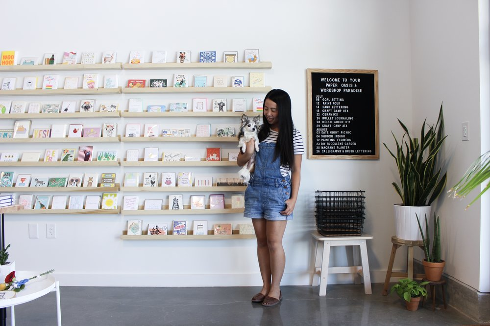 The Paper + Craft Pantry owner, Pei, and her pup Harley standing in front of our new card wall.