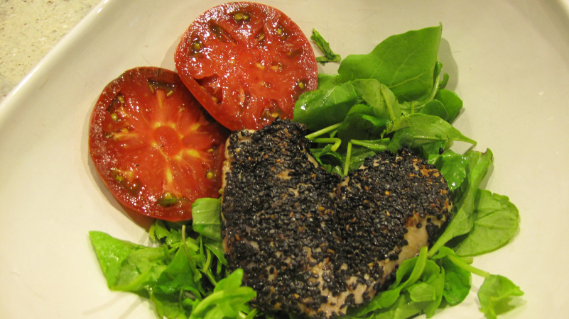 Black sesame encrusted tuna and truffled heirloom tomatoes on bed of arugula.