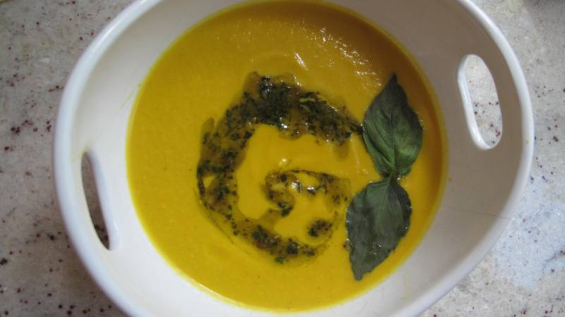 Carrot Ginger Cashew Bisque with vegan pesto and basil leaves.