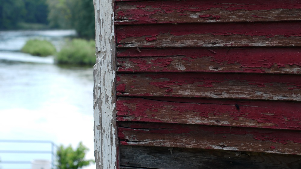 Picture of a weathered red clapboard building wall