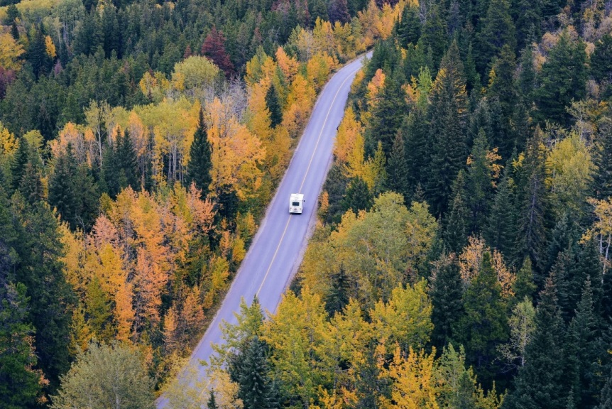 Aerial view of two-lane highway cutting through forest with RV driving on it