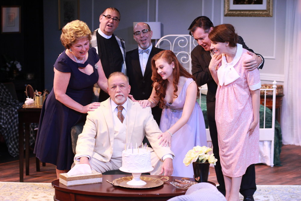 Big Daddy (Frank Mastrone), seated, Big Mama (Cynthia Hannah), Reverend Tooker (Jim Schilling), Doc Baugh (Jeff Gurner), Maggie (Andrea Lynn Green), Gooper (Robert Morley), Mae (Elizabeth Donnelly) in Music Theatre of Connecticut's production of Cat on a Hot Tin Roof