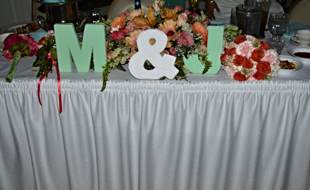 "The Couple's sweetheart table. The ""M&J"" handcrafted using canvas 3D letters and symbol. ""M"" and ""J"" were painted using a mint green chalkboard paint and the ""&"" was covered with a laced linen paper found at a craft store."