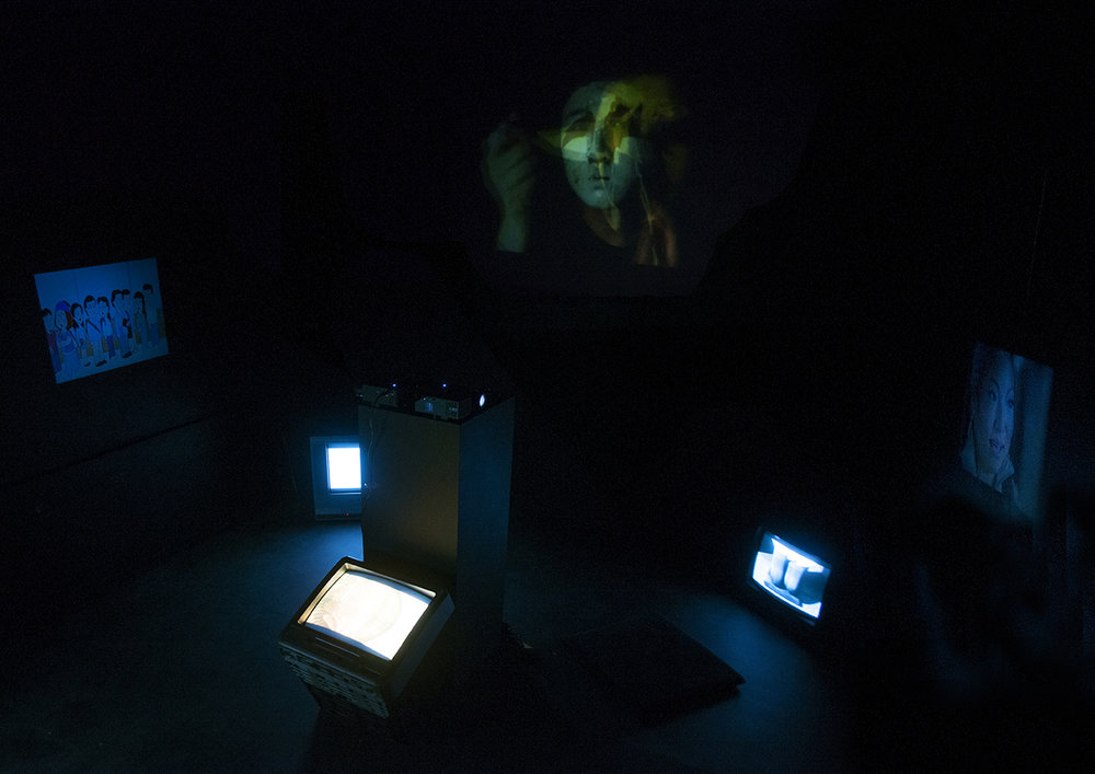 Hyphen (self-portrait)   Multimedia installation: projection, sound, television, DVDs in a constructed room 96x125x96 inches.  Installation view.