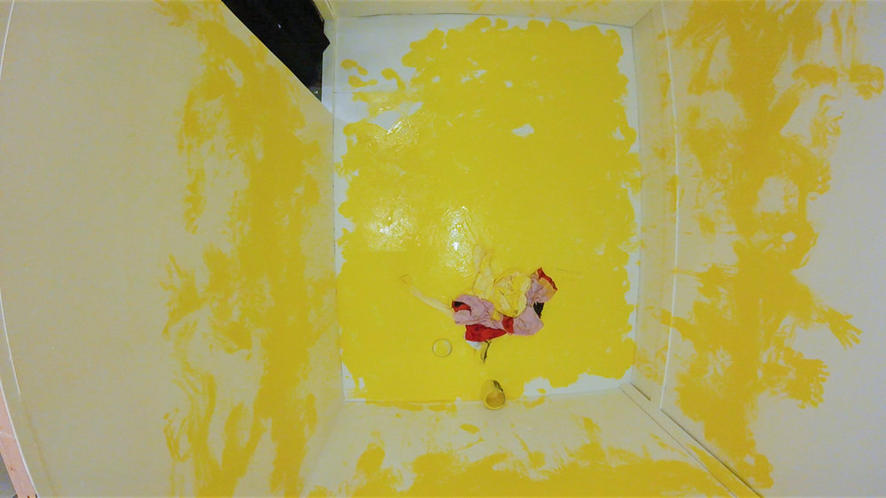 Marking. (AFTER the performance)  Multimedia installation: yellow paint, oriental kimono, Coverall, googles, face mask, paint can, and paint opener.  96x125x96 inches.  Installation view.
