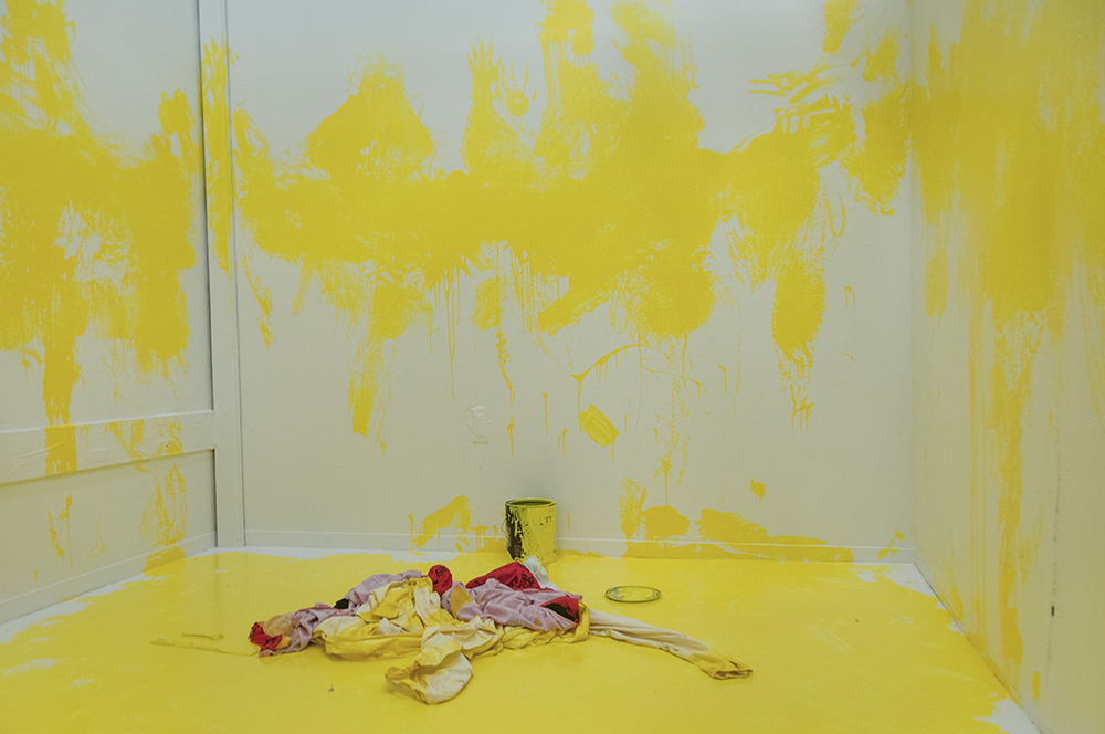 Marking.  Multimedia installation: yellow paint, oriental kimono, Coverall, googles, face mask, paint can, paint opener, documented performance, and television sets.  96x125x96 inches.  Installation view.