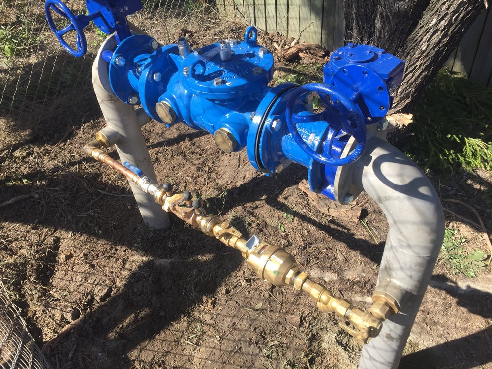 Above ground check valve and meter arrangement for unity water