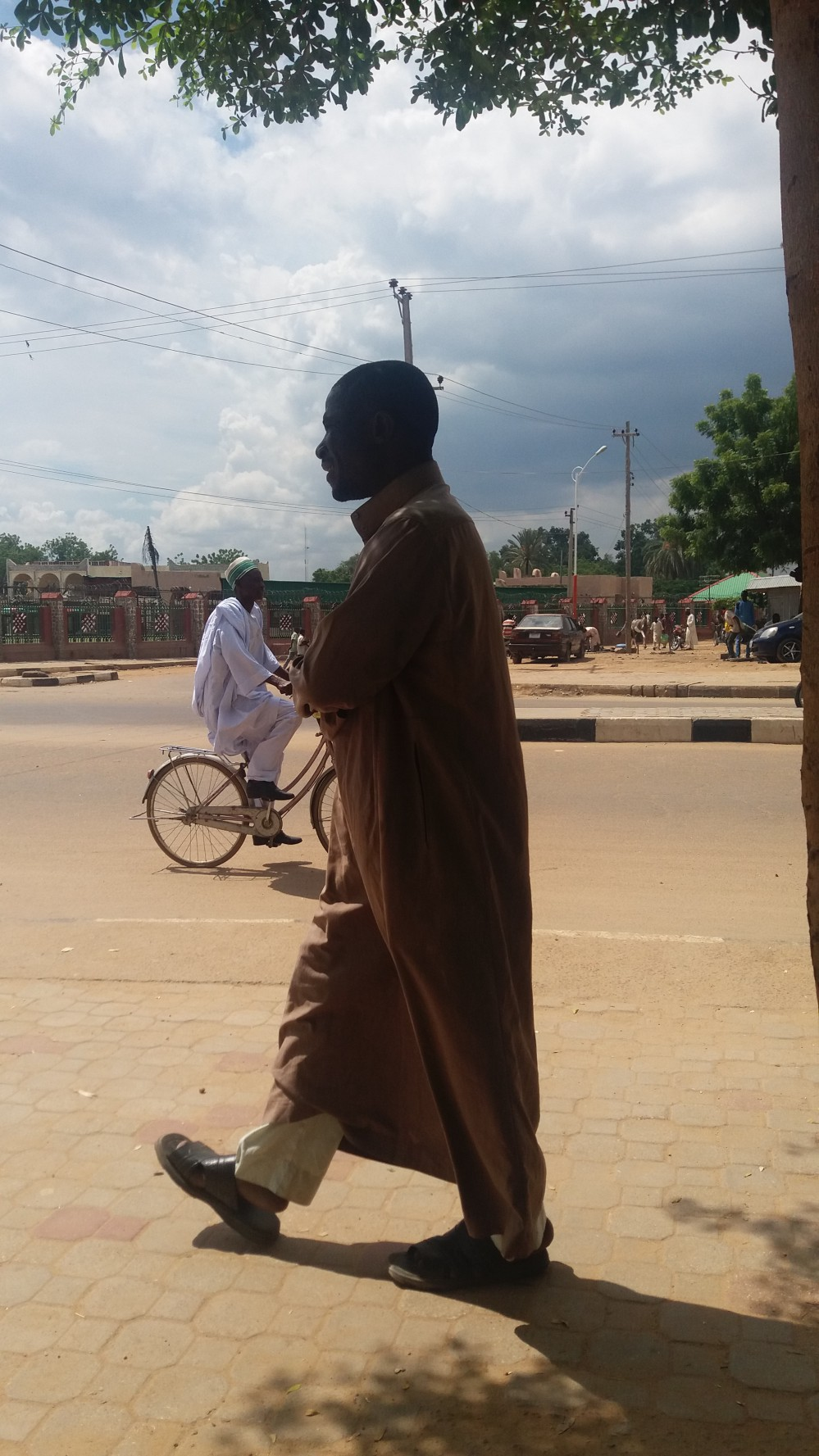 Man walking, dressed in Jalabia and another on Bike dressed in Agbada/Babaringa