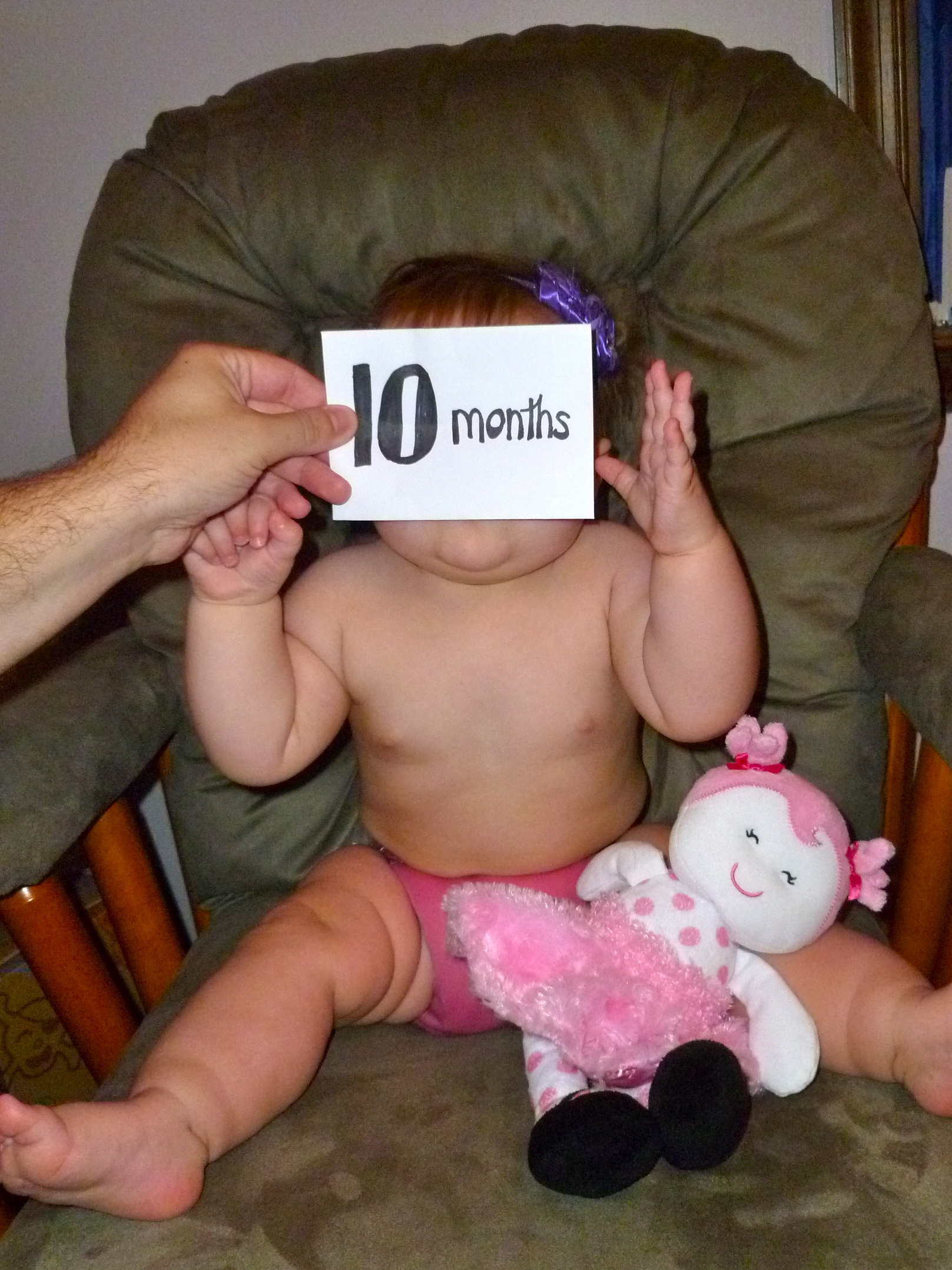 "Girl in a chair with a card over her face reading ""10 months"""