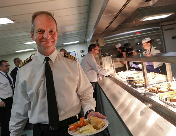 Commanding officer of HMS Queen Elizabeth, Captain Jeremy Kyd receives his first meal onboard.