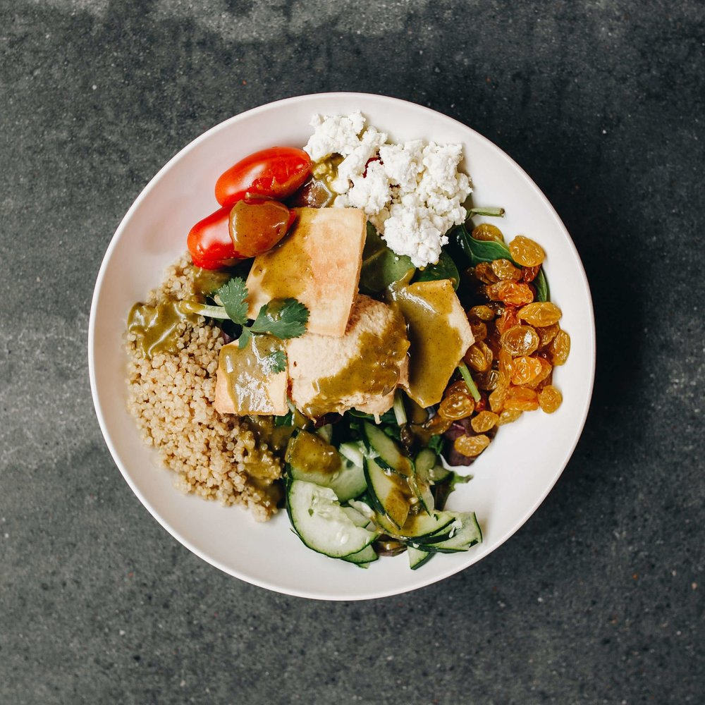 CLUB MED BOWL - Mixed greens, quinoa, feta, cucumbers, raisins, cilantro, tomatoes, lemon chicken, hummus, pita chips, zhoug (mediterranean chimichurri)11.14