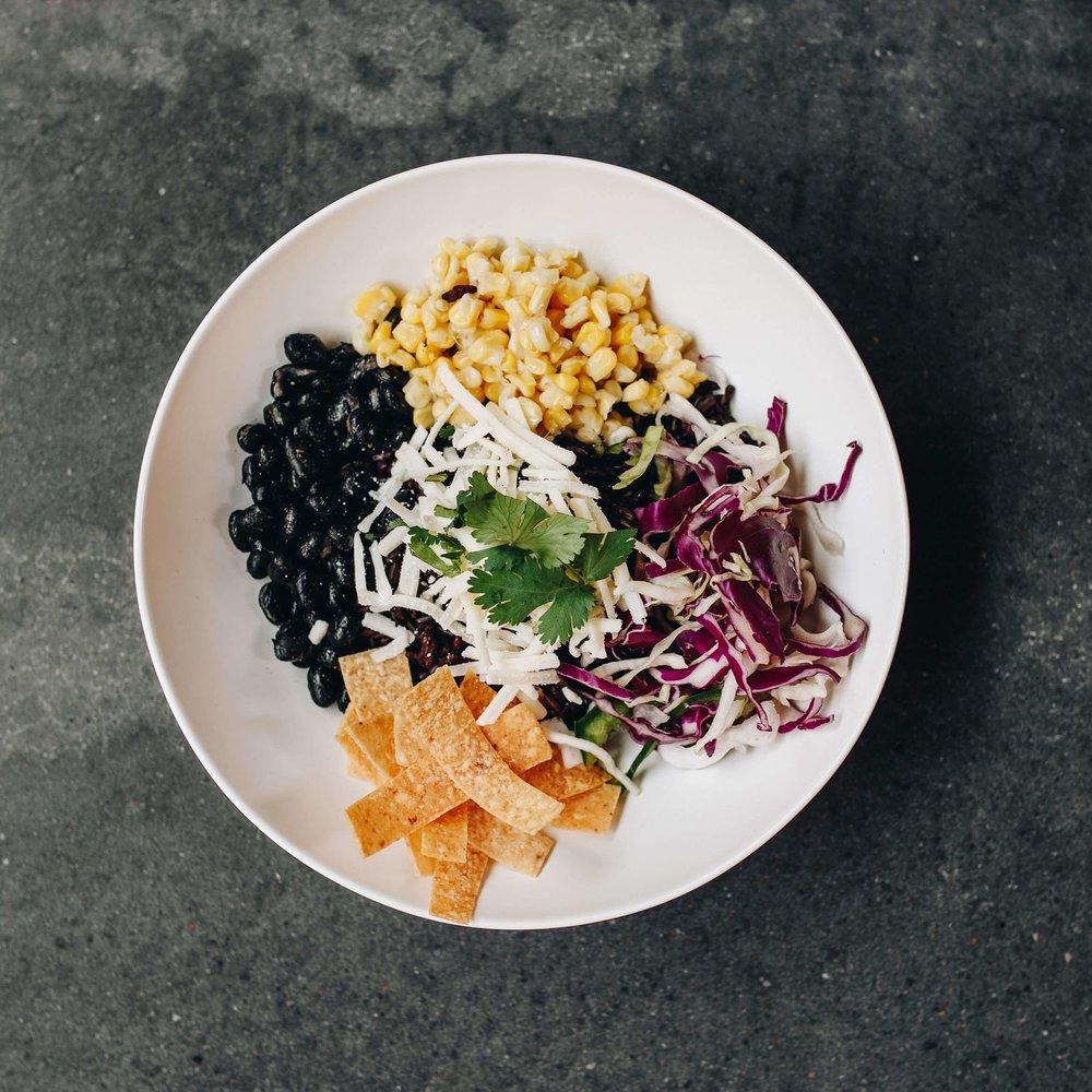 FIESTA BOWL - Black rice, black beans, local corn, cabbage poblano slaw, choice of tempeh or chicken, cheddar cheese, cilantro, corn tortilla, salsa roja10.43