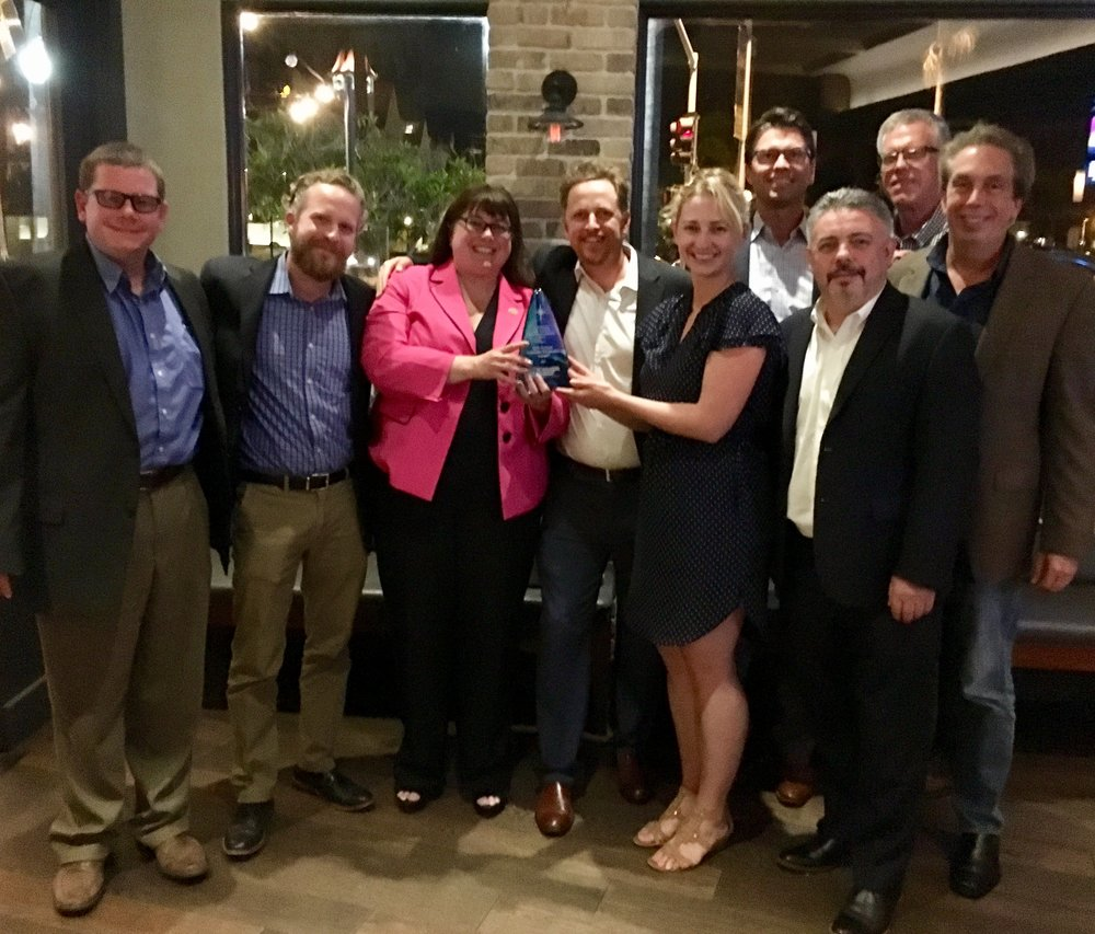 NASRC board members Clay Rohrer, Tristam Coffin, Keilly Witman, Aaron Daly, Todd Washburn, Bryan Beitler, Peter Narreau and Peter Dee pose with the award of the most recent board meeting.