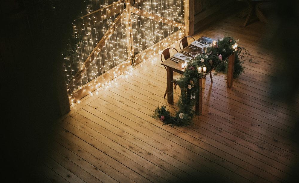 Flanagan farm maine wedding barn sweetheart table lights greens garland.jpg