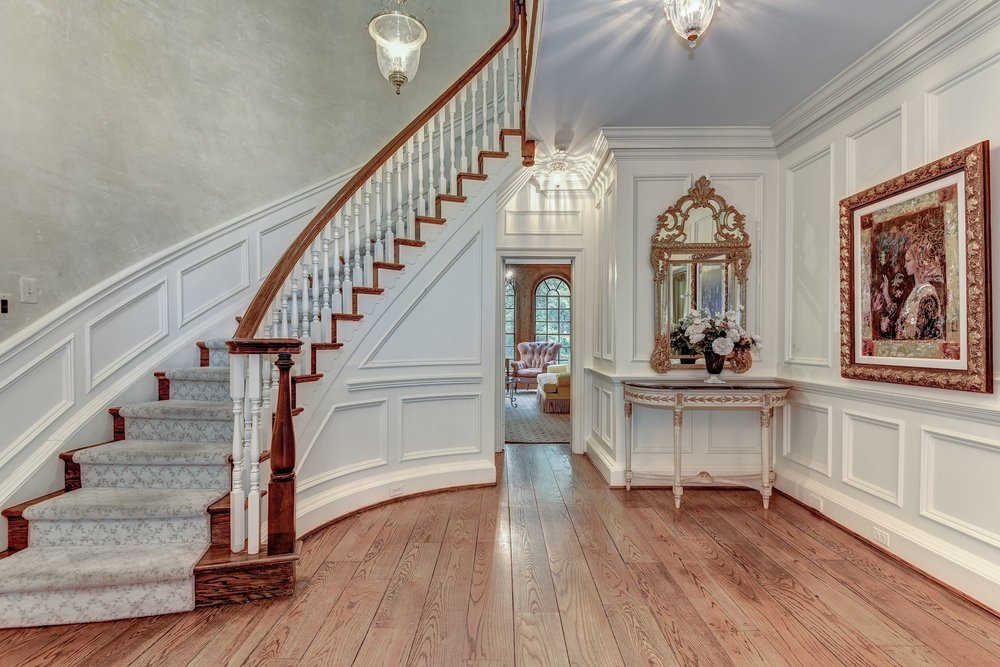 A spacious Foyer with curved stairway opens to the Living Room, Dining Room & Library