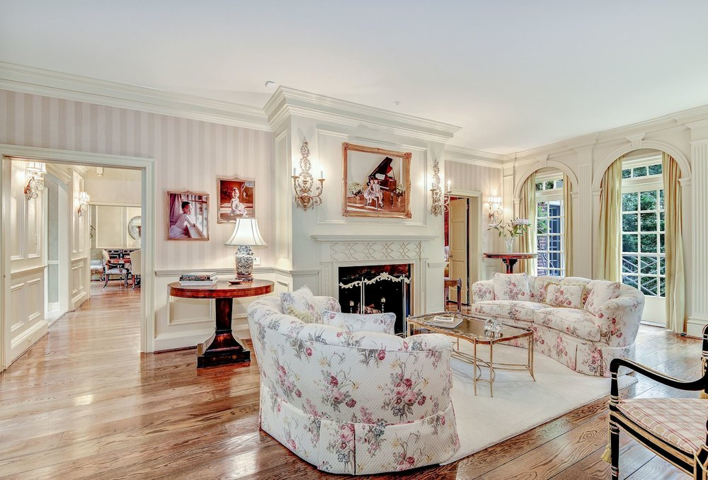 The elegantly appointed Living Room features a beautiful fireplace, custom millwork and access to a brick terrace overlooking the landscaped gardens, swimming pool and spa