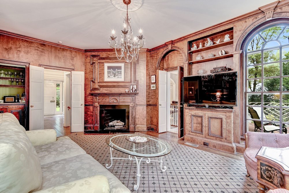 The paneled Library with wood-burning fireplace and wet bar is the perfect place to relax. It opens to a brick terrace