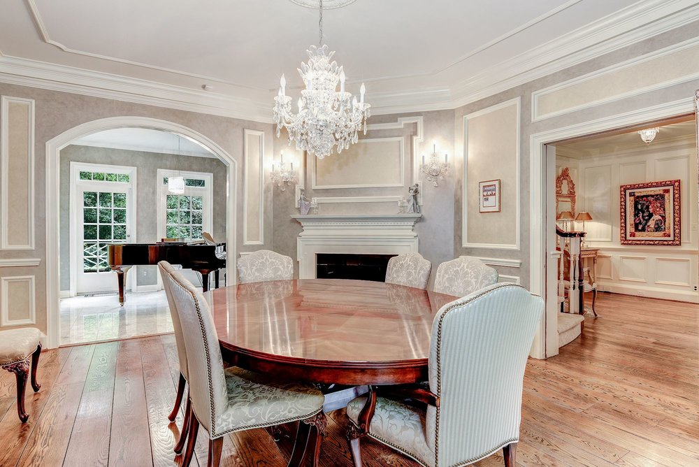 The elegant, spacious and bright formal Dining Room offers a fireplace and pocket doors