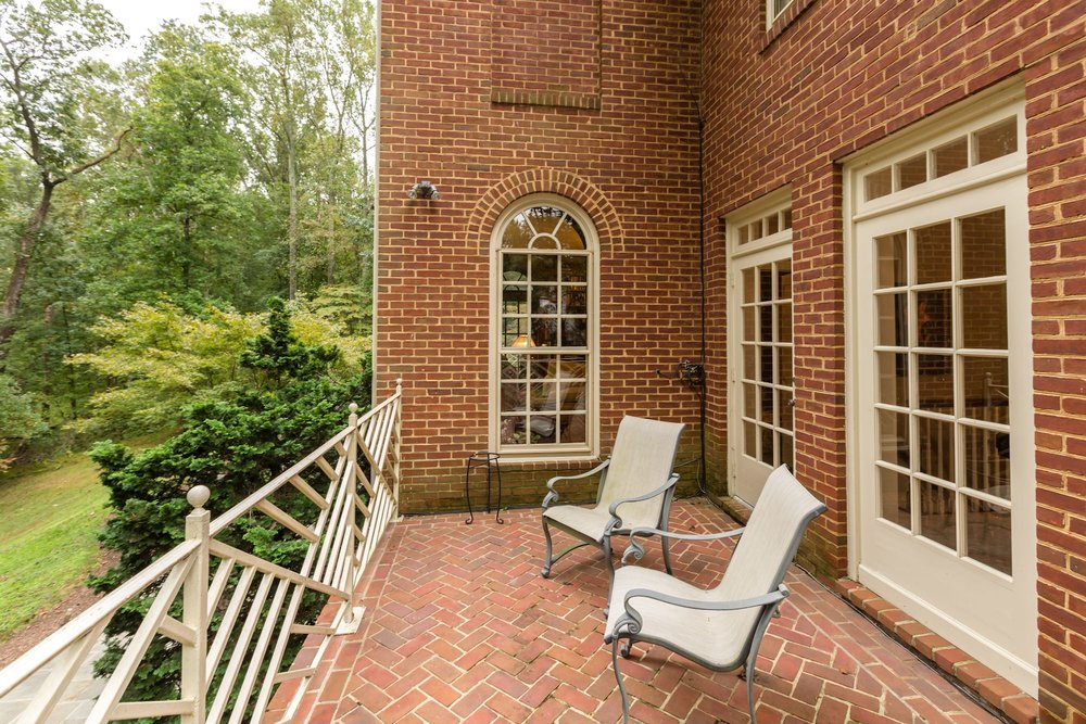 Herringbone brick terrace with Chinese Chippendale patterned wrought iron railing