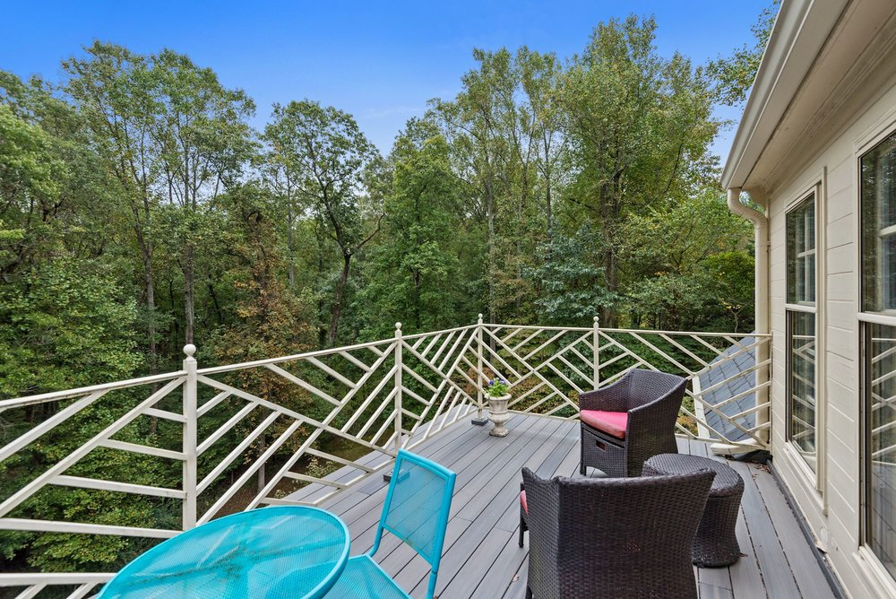 The upper level terrace offers captivating views over the property's two acres of woods and landscaped gardens