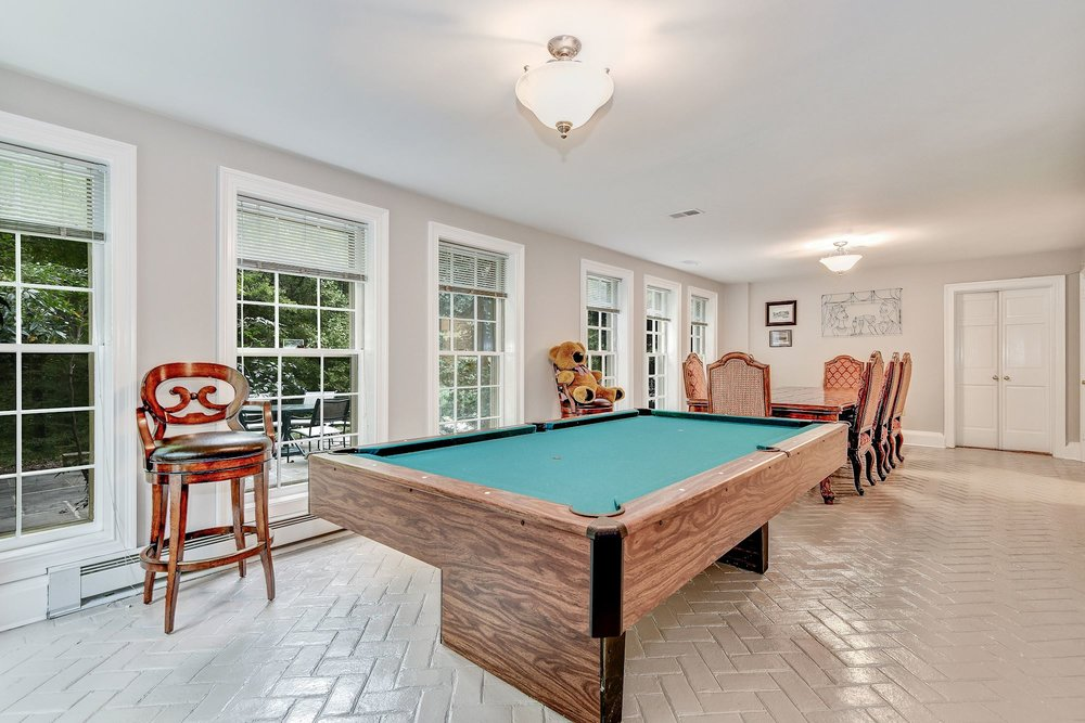 The Recreation Room features herringbone brick floors, a Kitchenette and opens to outdoor entertaining