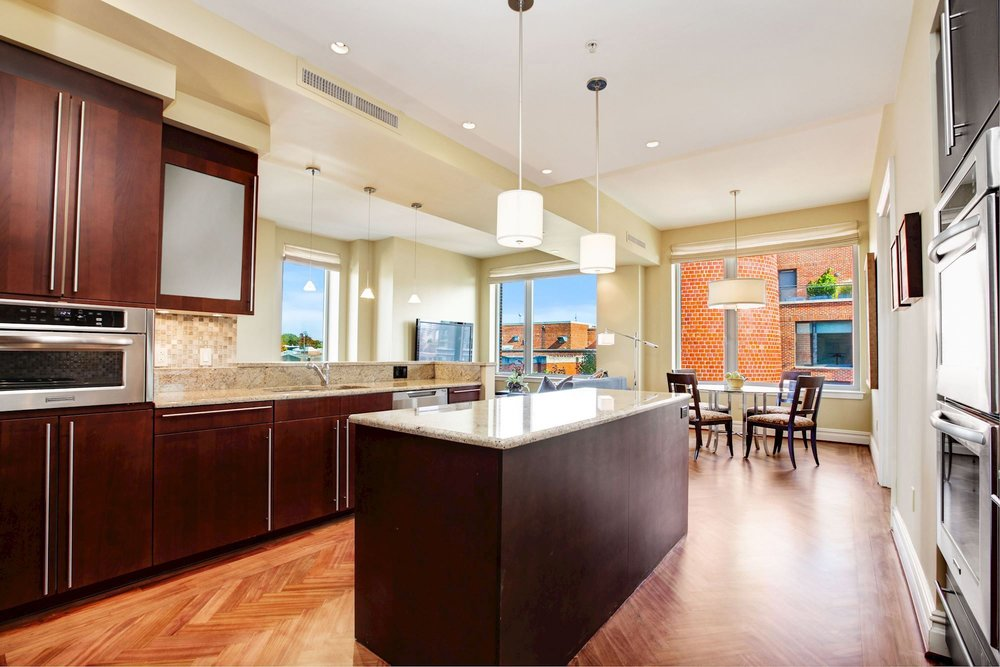 Kitchen offers Breakfast Bar and Opens to Informal Dining and Living Areas