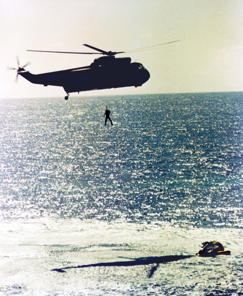 Gordon Cooper is hoisted into a helicopter before being flown to recovery ship, USS Lake Champlain