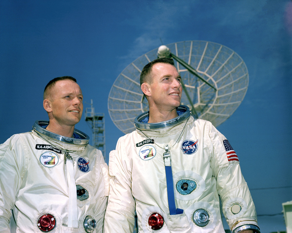 11 March 1966 - Astronauts Neil A. Armstrong (left), command pilot, and David R. Scott, pilot, the Gemini-8 prime crew, during a photo session outside the Kennedy Space Center (KSC) Mission Control Center. They are standing in front of a radar dish. Photo credit: NASA