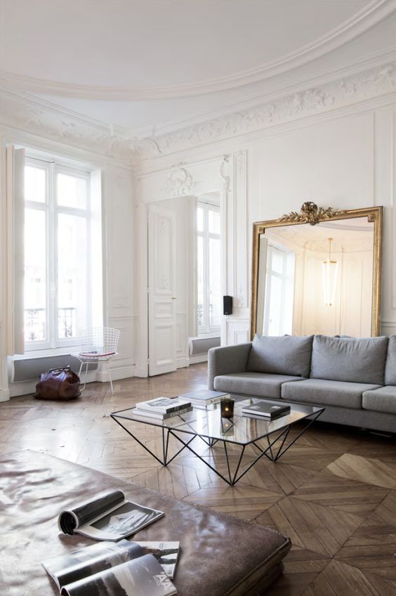 Great juxtaposition of the gilt antique mirror and starkly modern glass coffee table
