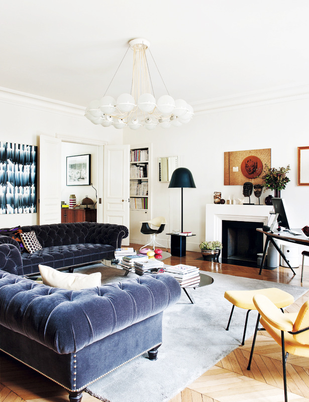 Love the use of the modern chandelier here to offset the chesterfields.