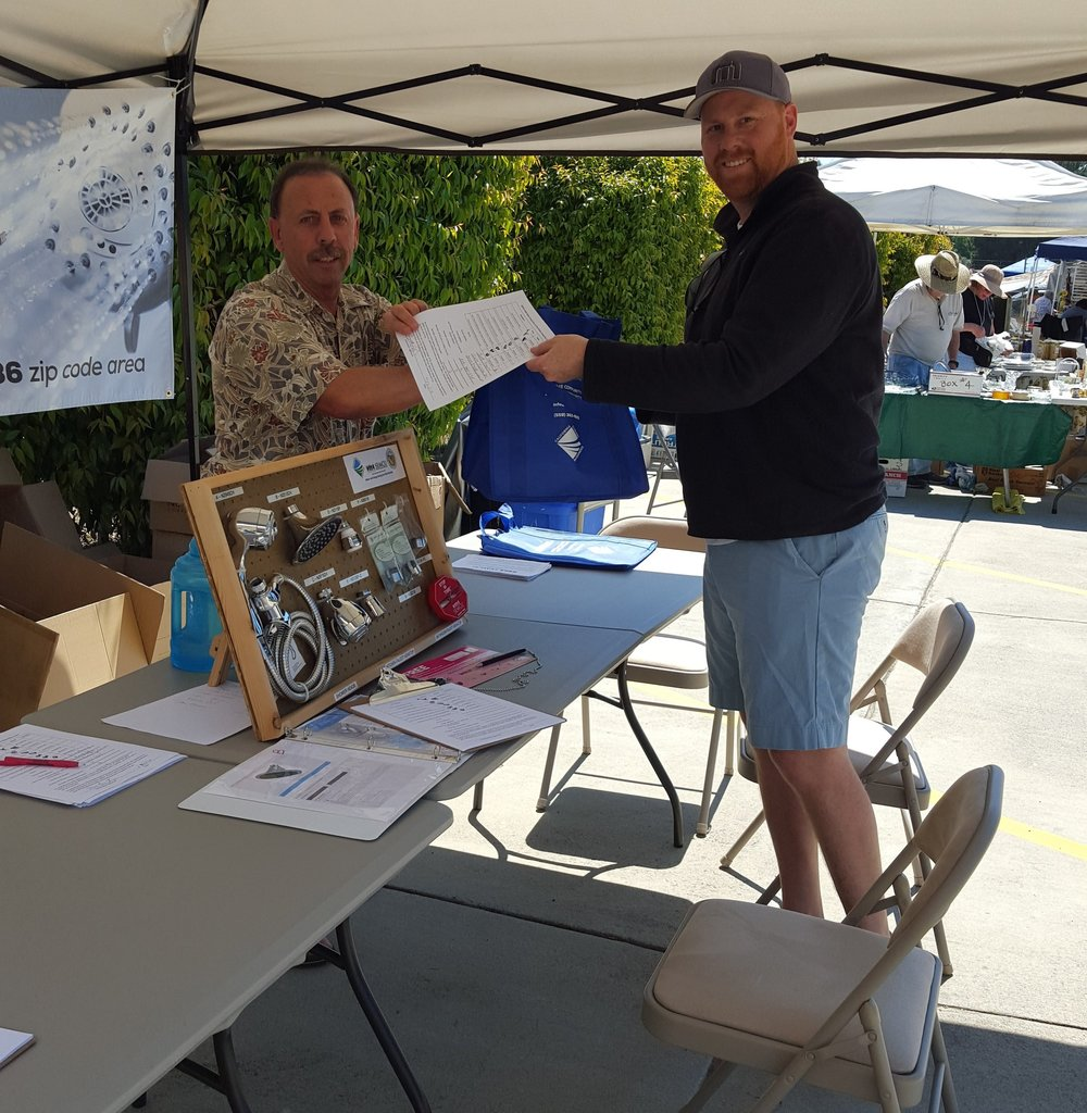 A SEMCU member distributes free water efficiency devices at an outreach event
