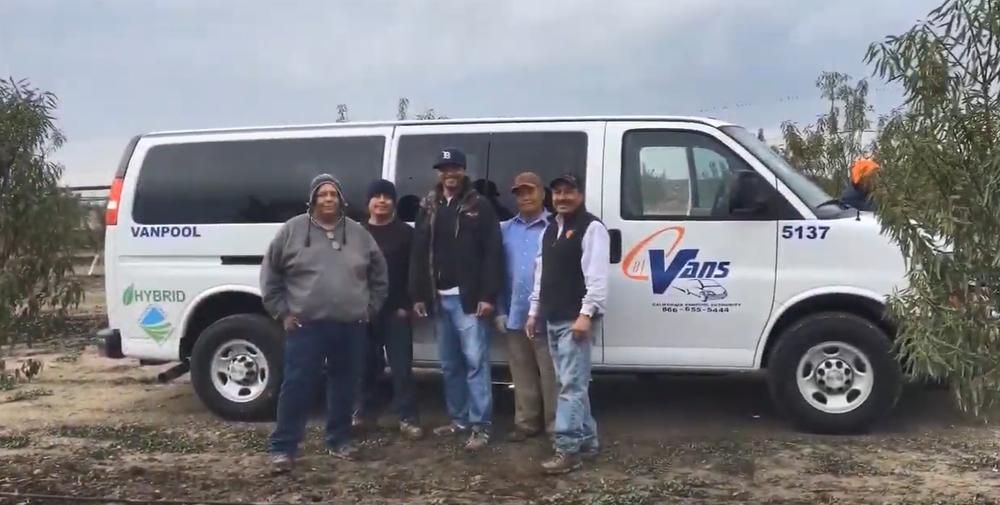 Farmworkers standing beside a CalVans hybrid vanpool vehicle